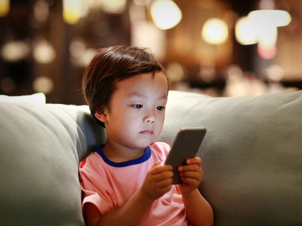 little-boy-looking-at-phone-on-couch.jpg